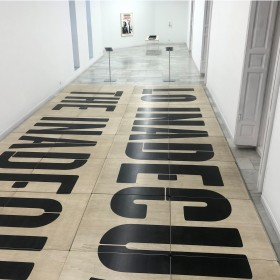"""""""Arena (Lo inadecuado)""""1. 40 tablas de madera de 100 x 100 cm., sobre estructura metálica     Medidas totales de la instalación: 412 x 1010 x 13 cm.  2. 2 expositores de pie con texto (c/u 112 cm. de altura)    Pieza única  2020"""
